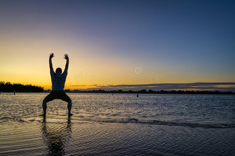 Sunrise silhouette of a man on a lake. Sunrise silhouette of a man standing in shallow water and practicing chigong or tai chi movements, Boyd Lake State Park in stock image
