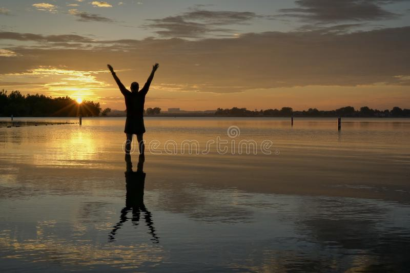 Sunrise silhouette of a man on a lake. Sunrise silhouette of a man standing in shallow water and  stretching or practicing chigong movements, Boyd Lake State stock photo