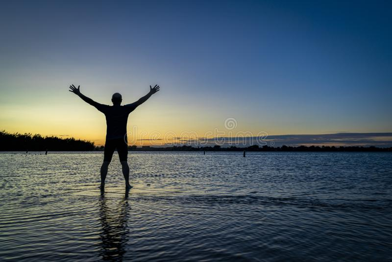 Sunrise silhouette of a man on a lake. Sunrise silhouette of a man standing in shallow water and  stretching or practicing chigong movements, Boyd Lake State stock photos