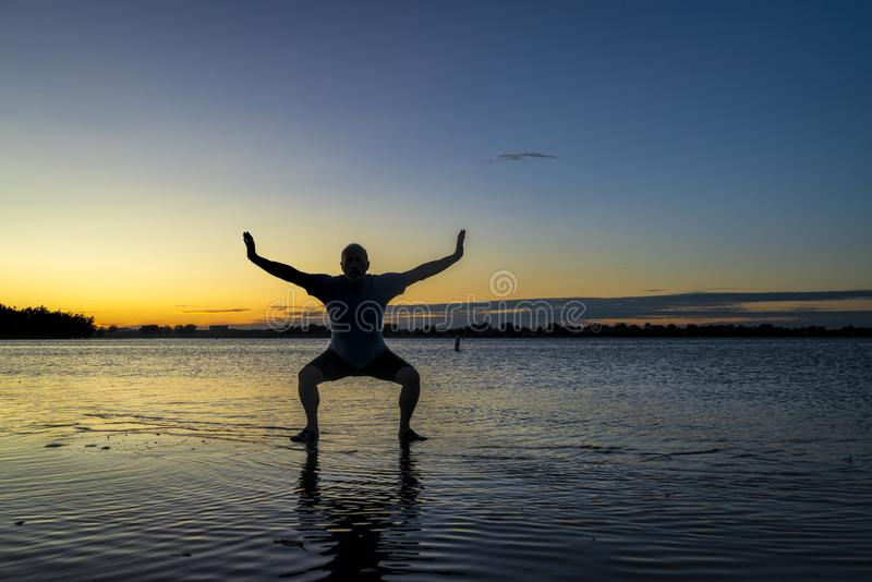 Sunrise silhouette of a man on a lake. Sunrise silhouette of a man standing in shallow water and practicing chigong or tai chi movements, Boyd Lake State Park in stock photo