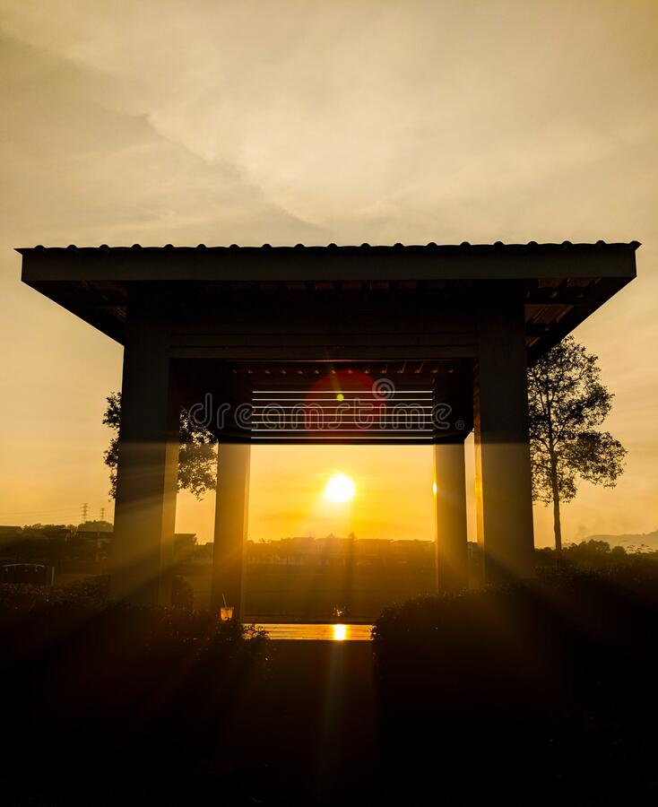 Sunrise with silhouette of trees and gazebo with sunray royalty free stock photography
