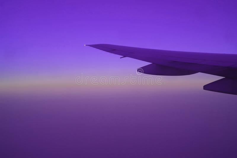 Sunrise sky with airplane wing seen from plane window during flight in vibrant purple color. Background stock photos
