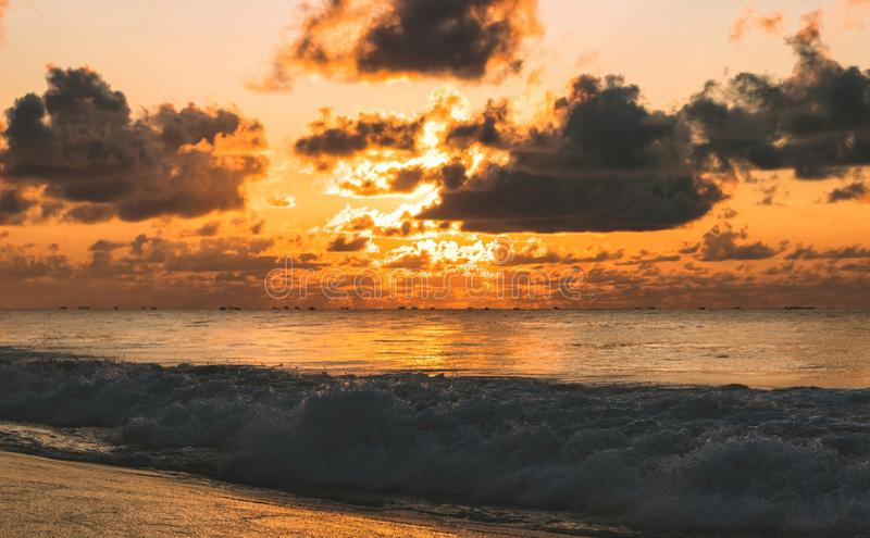 Sunrise sky at puri India med en gyllene atmosfär med mörka moln och frontalvågor som bryter mot kusten royaltyfri bild