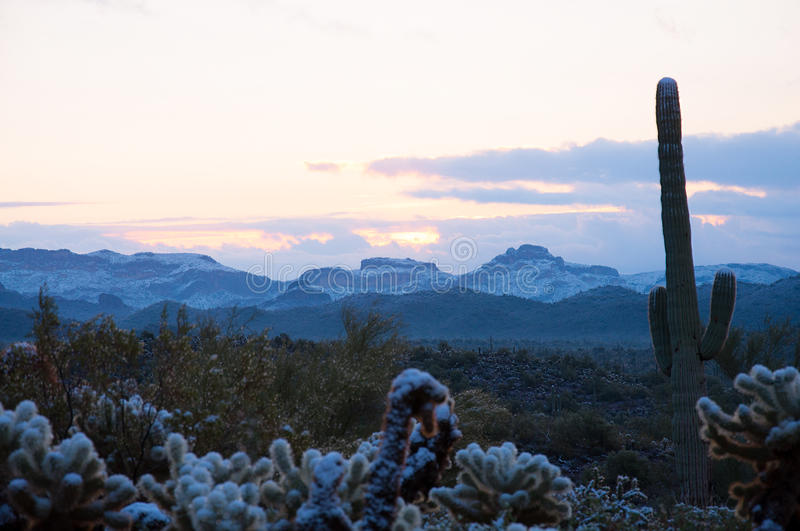 Sunrise in the snow-capped Superstition Mountains of Arizona. The first daybreak of the first day of a new year with fresh unexpected snow in the desert royalty free stock image