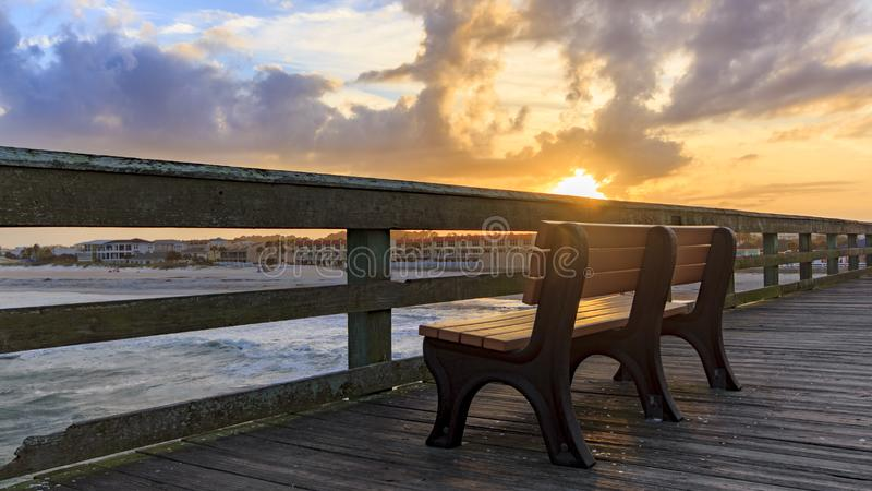 Sunrise, St. Johns County Ocean Pier, St. Augustine, Florida. Sun rising over empty bench on St. Johns County Ocean Pier in St. Augustine, Florida stock photo