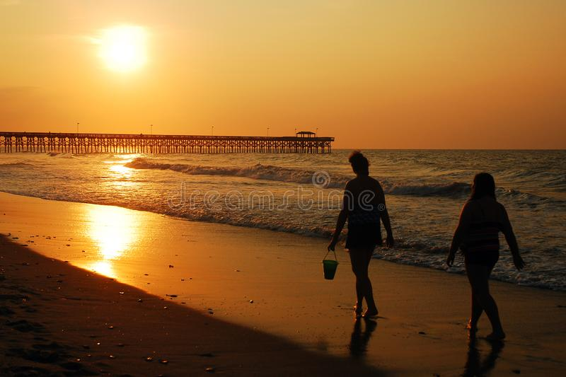 Sunrise Stroll along the coast. Two women take a Sunrise Stroll along the coast at Myrtle Beach, South Carolina royalty free stock image