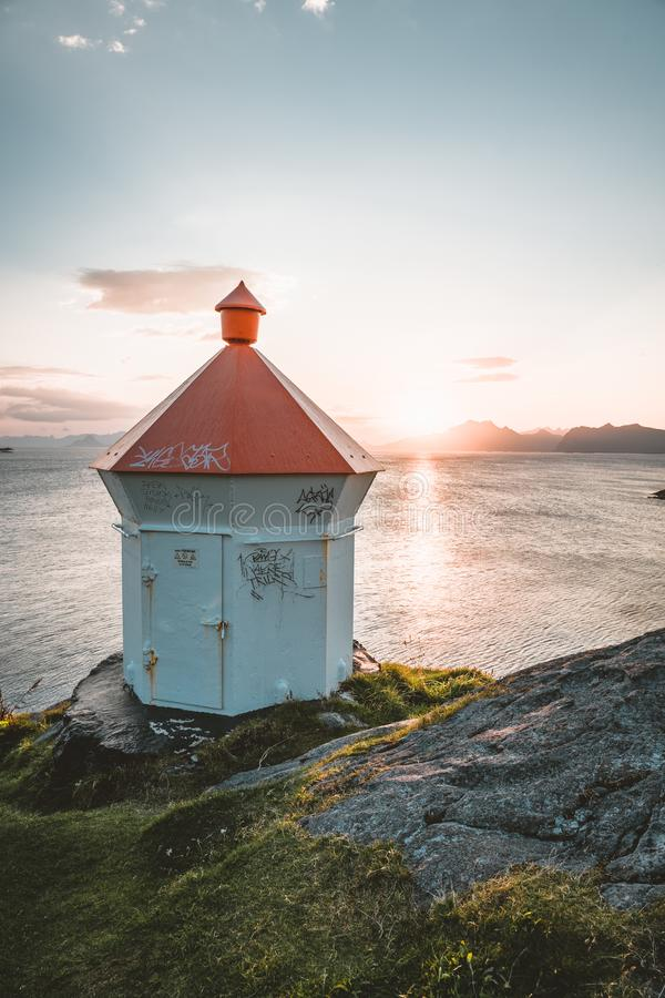 Sunrise and Sunset at Henningsvaer light house, fishing village located on several small islands in the Lofoten. Archipelago, Norway over a blue sky with clouds stock photo