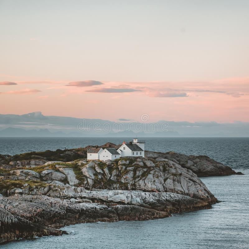Sunrise and Sunset at Henningsvaer lighthouse with pink sky. The small fishing village located on several small islands. In the Lofoten archipelago, Norway over stock photography