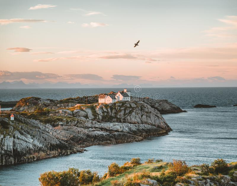 Sunrise and Sunset at Henningsvaer lighthouse with pink sky. The small fishing village located on several small islands. In the Lofoten archipelago, Norway over royalty free stock image