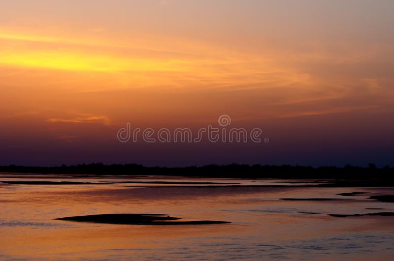Sunrise sunset. Sunrise over the river. golden waves in the rays of the rising sun royalty free stock photography