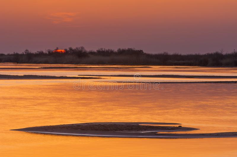 Sunrise sunset. Sunrise over the river. golden waves in the rays of the rising sun stock image