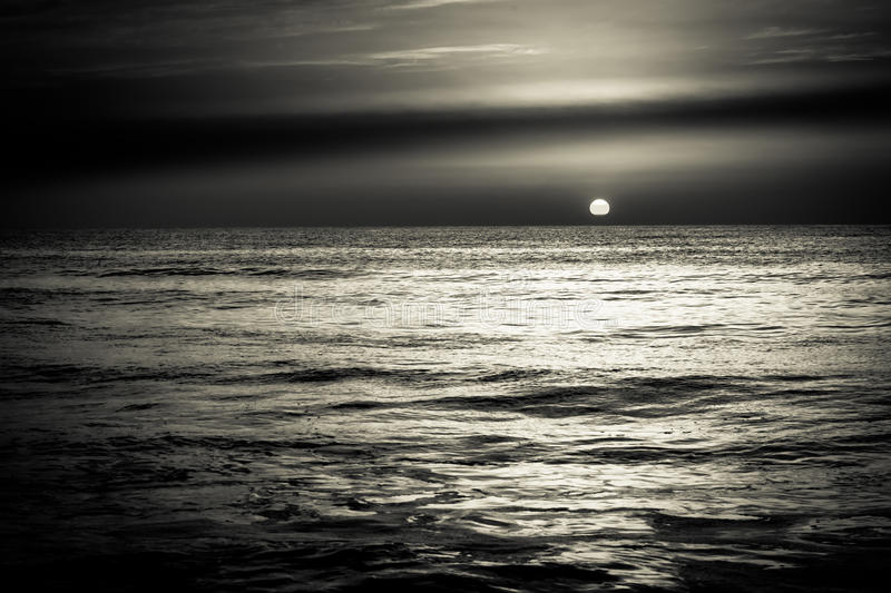 Sunrise sunset over the sea ocean waves in black and white stock images