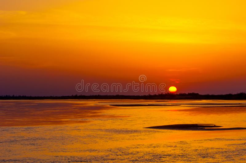 Sunrise sunset. Sunrise over the river. golden waves in the rays of the rising sun royalty free stock image