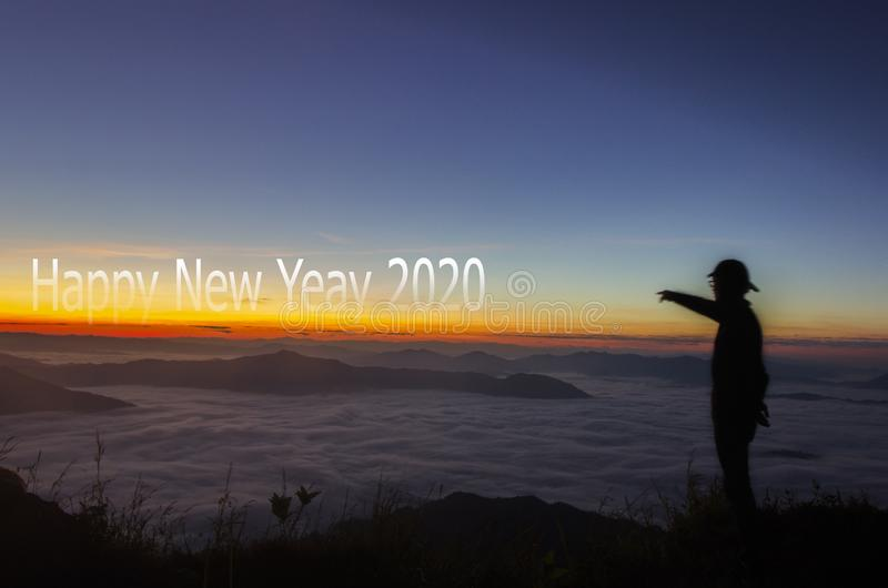 Sunrise with text Happy New Year 2020 celebration concept. Sunrise with text words Happy New Year 2020 celebration with silhouette man on top of mountain for stock photography