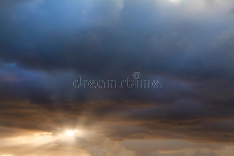 Sunrise though storm clouds. Stunning sunset cloudscape with dark clouds, story evening weather royalty free stock photos