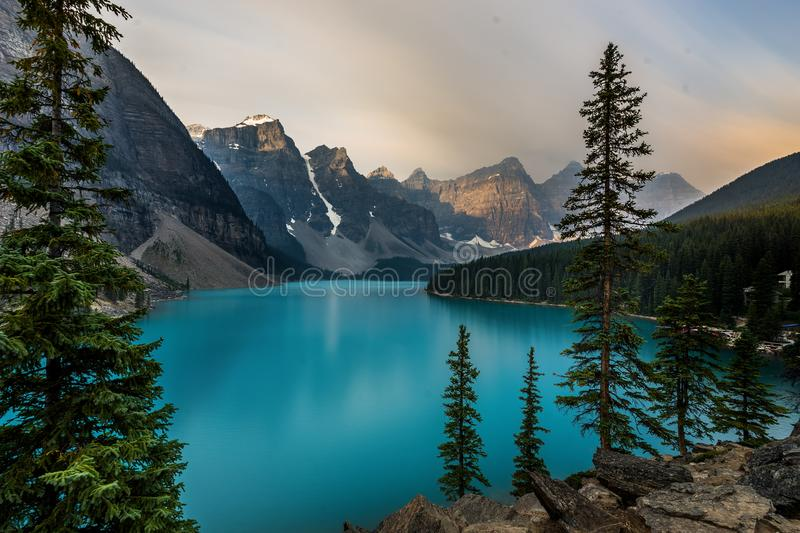 Sunrise with turquoise waters of the Moraine lake with sin lit rocky mountains in Banff National Park of Canada in. Valley of the ten peaks. Photo taken in stock photo