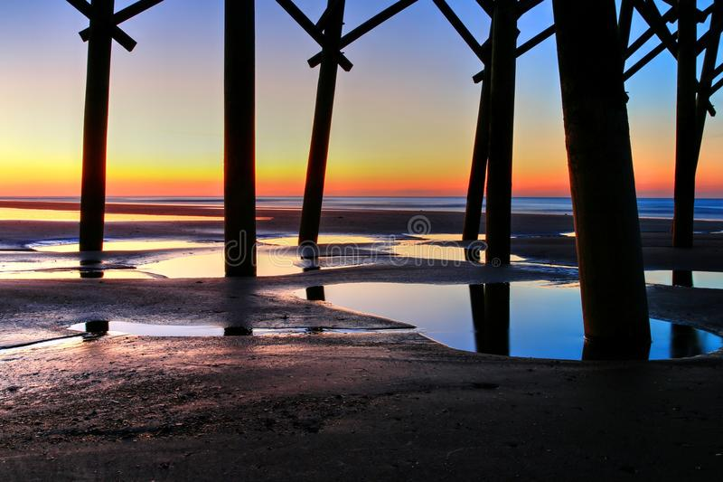 Sunrise Under Folly Beach Pier. Under Folly Beach Pier in Charleston, South Carolina where light and reflection in the tidal pools became important to me more royalty free stock photos