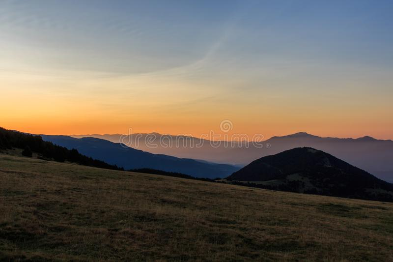 Sunrise from a valley watching the mountains with a little fog. stock image