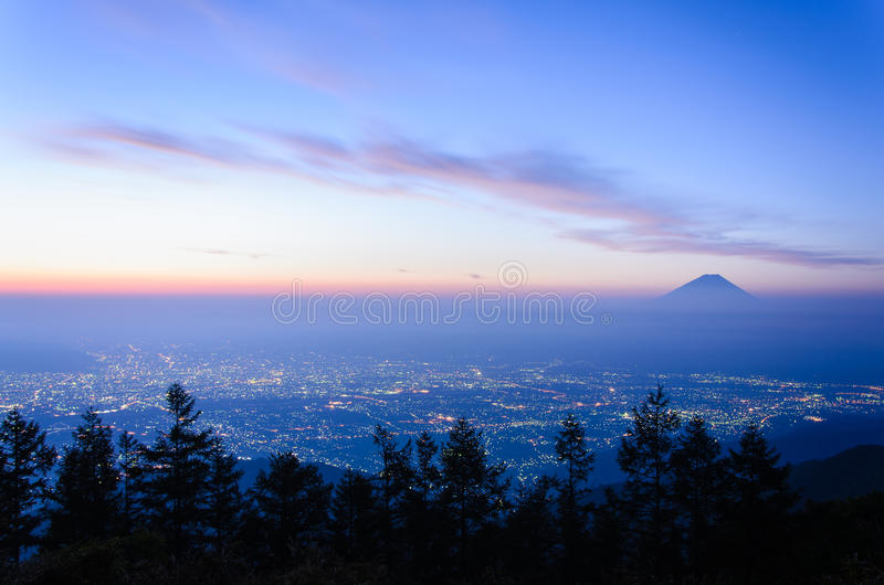 Sunrise View of the Kofu city and Mt.Fuji. View of the Kofu city and Mt.Fuji in early morning. The city is glowing in the bottom royalty free stock photos