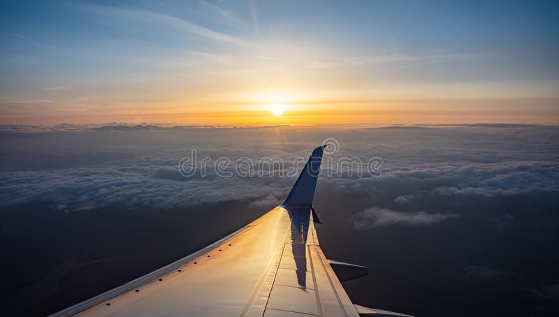 Sunrise view out of an airplane window. Plane flying over the clouds royalty free stock photo