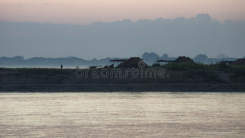 Sunrise at a village at the Irrawaddy. Sillhouettes of a village and an old man along the river Irrawaddy during sunrise, Myanmar stock image