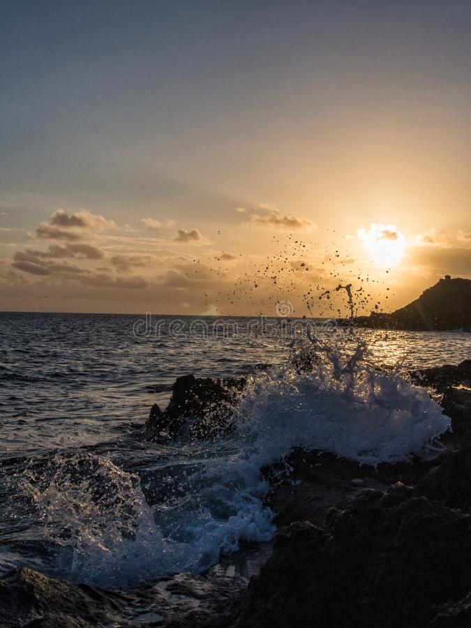 Sunrise wave breaks on the rock, Pantelleria, Italy royalty free stock images