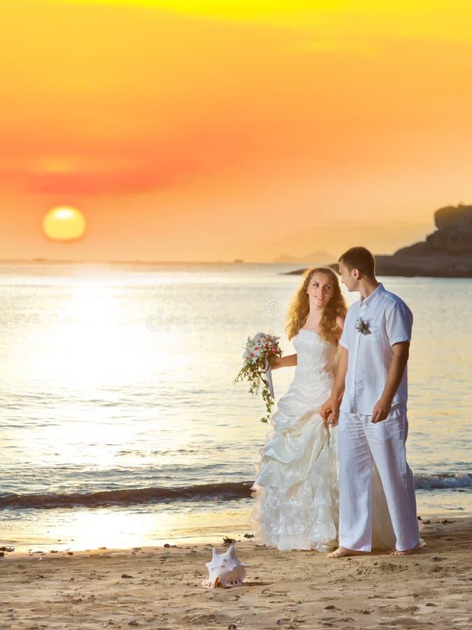Sunrise wedding. Bride and groom walking on the beach at sunrise royalty free stock photos