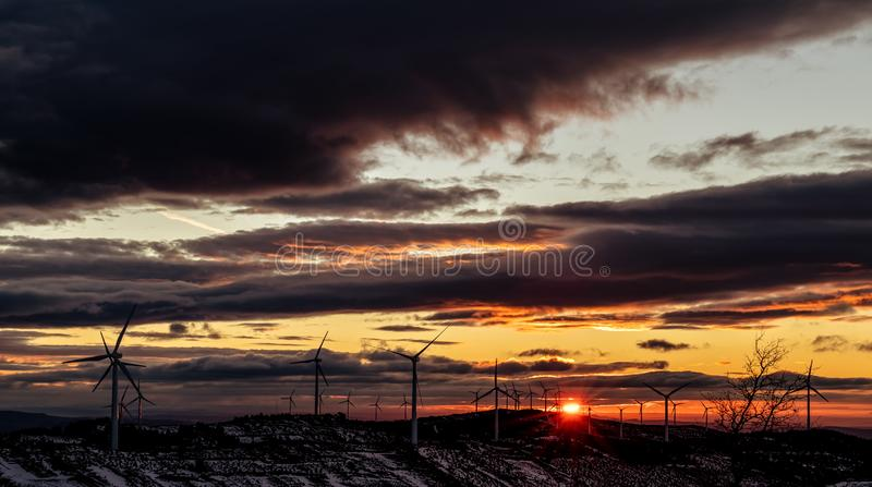 Sunrise in a wind field with clouds and sun in the background royalty free stock images