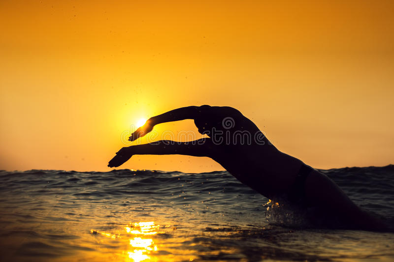 Sunrise, young man swiming in the sea royalty free stock photography