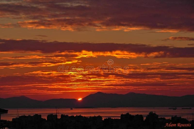 Sunrises sunsets in a ocean. Red colored sky with mountains and lakes stock photos
