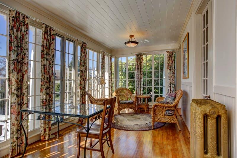 Sunroom brillante con muebles de mimbre imagenes de archivo