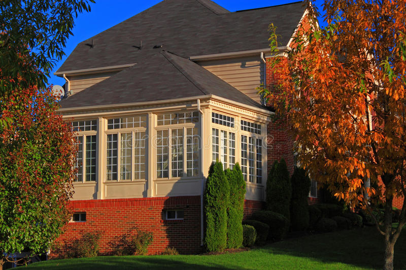 Sunroom. Luxury house with big sunroom at suburban residential community in Autumn with colorful leaves stock photo