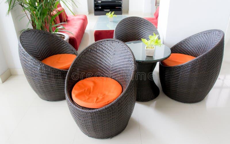 Sunroom nella casa di lusso con mobilia di vimini immagini stock