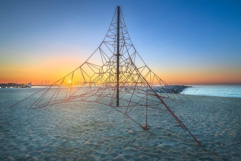 Sunrset alaranjado na praia com grade do jogo, Barcelona fotografia de stock