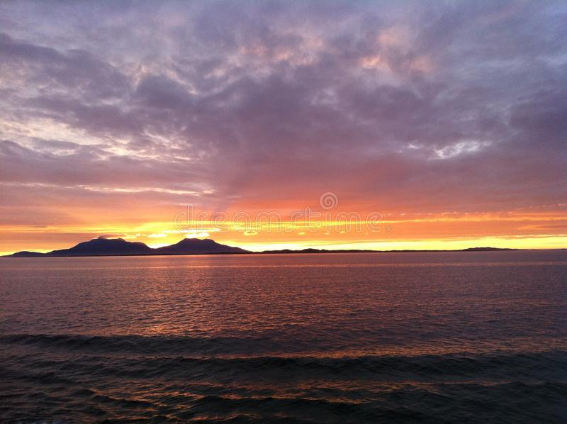 The Suns Naptime. Beautiful sunset in Northern Norway seen from a coastal going ship stock photo