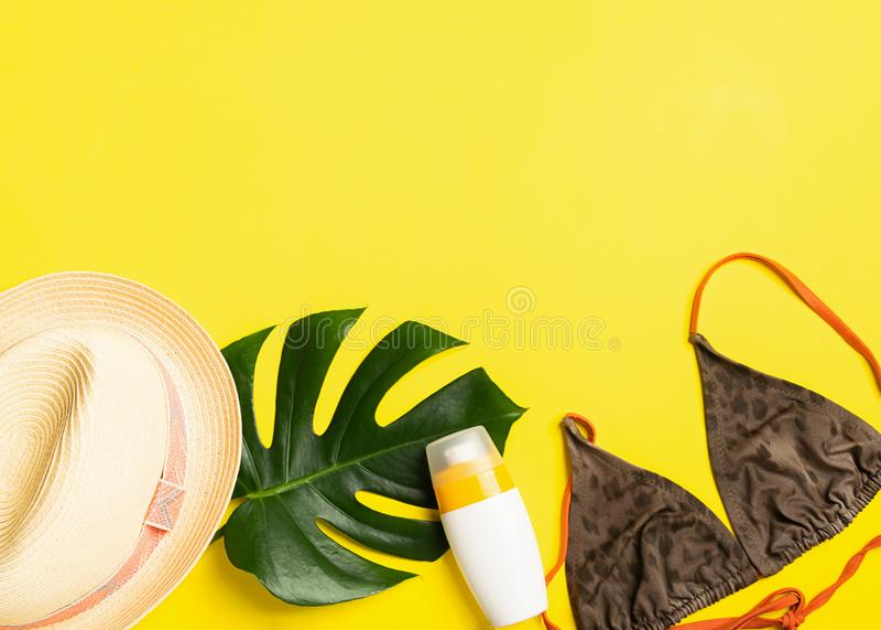 Sunscreen εξαρτημάτων θερινών παραλιών φωτεινό κίτρινο υπόβαθρο μαγιό θερινών καπέλων Έννοια και παραλία καλοκαιρινών διακοπών στοκ εικόνες με δικαίωμα ελεύθερης χρήσης
