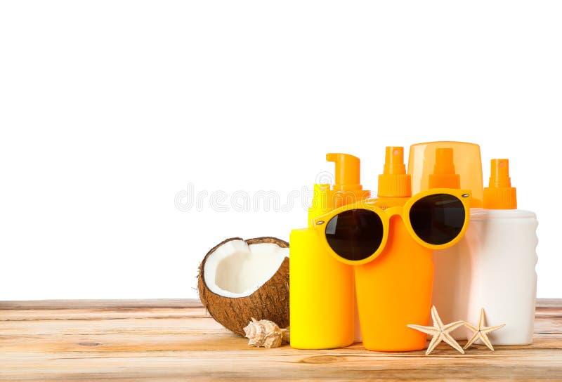 Sunscreen ψεκασμοί με τους αστερίες, την καρύδα και τα γυαλιά ηλίου στον ξύλινο πίνακα που απομονώνεται στο άσπρο υπόβαθρο στοκ φωτογραφίες με δικαίωμα ελεύθερης χρήσης