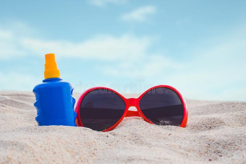 Sunscreen eller sunblocklotionflaska med solglasögon på stranden royaltyfri foto