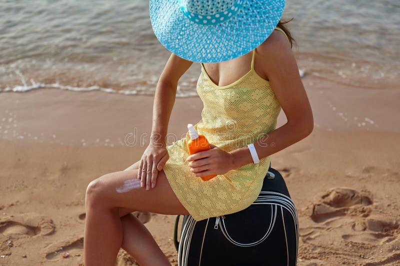 Sunscreen och härlig kvinnlig fot i sommarpölen, begreppet av skydd av huden royaltyfria bilder
