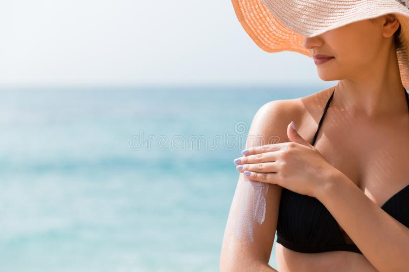 Sunscreen sunblock. Woman in a hat putting solar cream on shoulder outdoors under sunshine on beautiful summer day stock photography