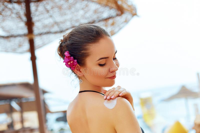 Sunscreen woman. Girl putting sun block on beach holding white sun tan lotion bottle stock photo