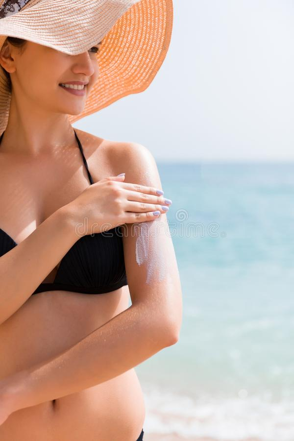 Sunscreensunblock Kvinna i en hatt som utomhus s?tter sol- kr?m p? skuldra under solsken p? h?rlig sommardag fotografering för bildbyråer