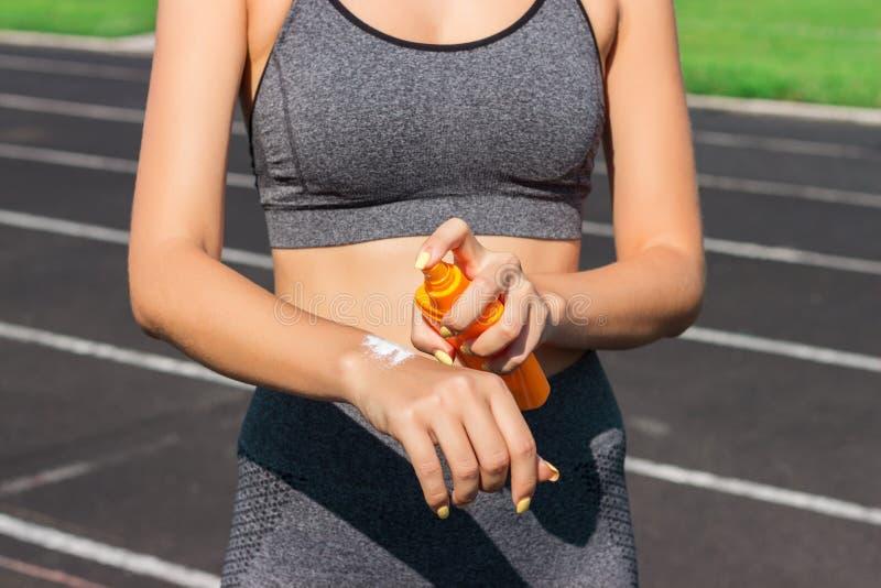 Sunscreensunblock Kvinna i en sportswear som sätter sol- kräm på skuldra på härlig sommardag Sportig kvinna som applicerar sunscr arkivfoto