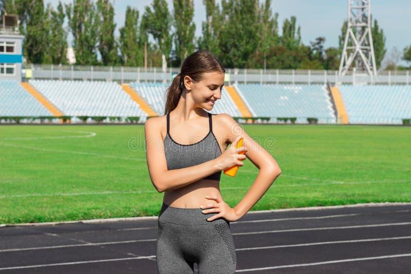 Sunscreensunblock Kvinna i en sportswear som sätter sol- kräm på skuldra på härlig sommardag Sportig kvinna som applicerar sunscr royaltyfri bild