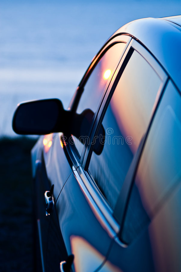 Sunse reflected in car. A view of a car parked at an oceanside overlook with the last rays of sunlight reflecting in the windows