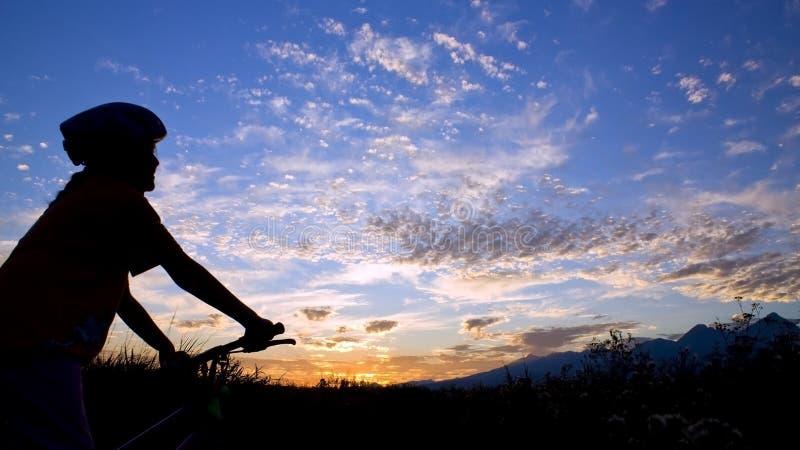 Sunset. Biker girl silhouette in sunset stock photography
