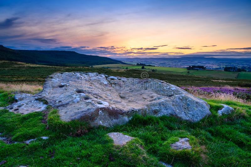 Sunset above Lordenshaws Hillfort Rock Art. Lordenshaws Hillfort is located near Rothbury in Northumberland National Park and has several large stones with stock photography