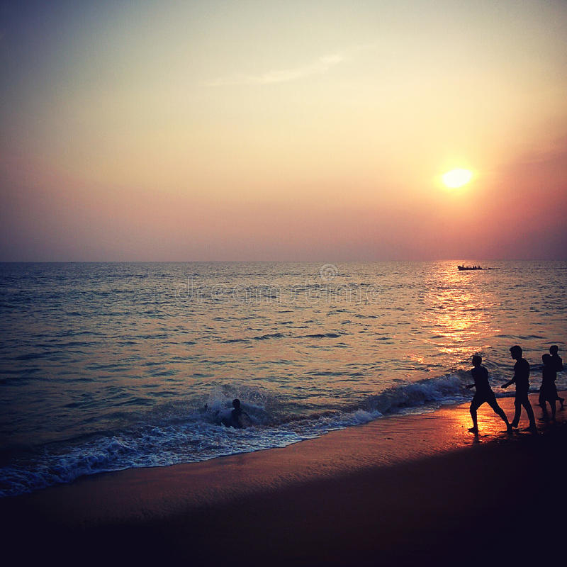 Sunset above the ocean with silhouette of children. Indian Ocean near Kovalam stock photos