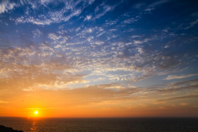 Sunset above the sea landscape panorama with full yellow sun reflections over the Atlantic Ocean and beautiful blue sky with white stock photos