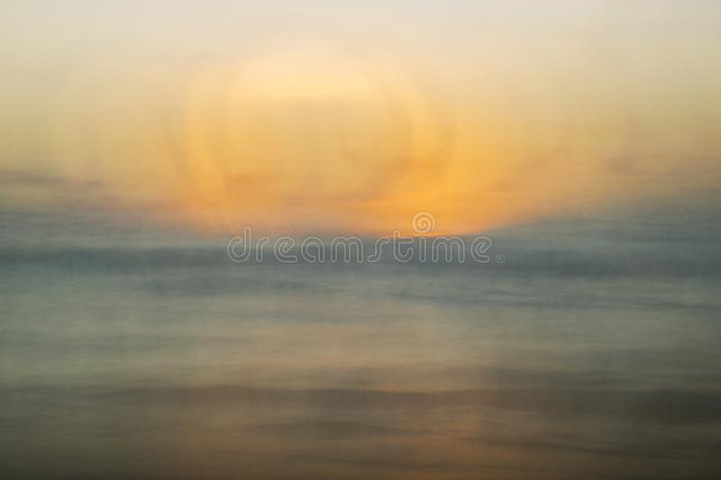 Sunset Abstract over Ocean in Muted Orange and Blue with Blur royalty free stock photos